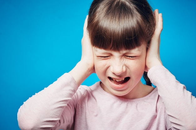 Portrait of a screaming girl with tightly shut eyes. child covering ears with hands
