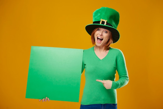Portrait of screaming leprechaun pointing at banner