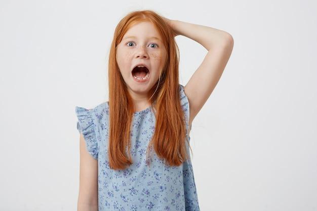 Ritratto di urlando petite lentiggini ragazza dai capelli rossi, indossa un abito blu, sembra arrabbiato, si erge su sfondo rosa.