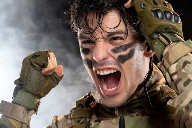 Portrait of screaming young soldier in camouflage on dark wall