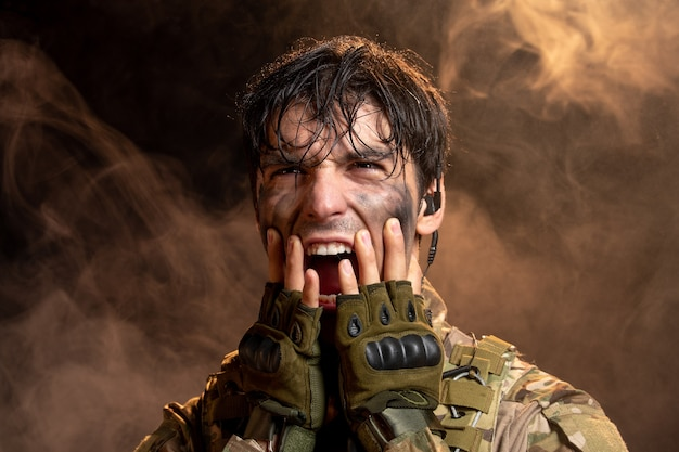 Portrait of screaming young soldier in uniform on dark wall