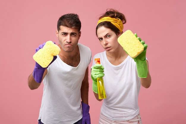 Portrait of scrupulous couple wearing protective gloves and white t-shirts holding sponges and detergent having concentrated look trying to clean everything qualitatively while cleaning windows