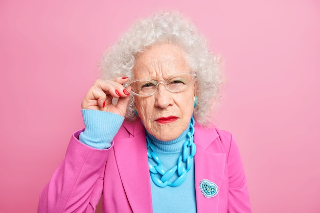 Portrait of scrupulous granny has attentive gaze, bad eyesight keeps hand on rim of spectacles dressed in fashionable clothes always cares about her appearance poses indoor. old style concept