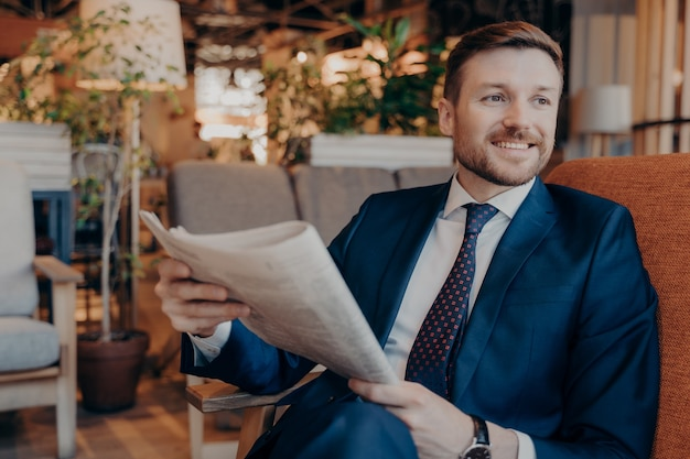 Portrait of seated successful young entrepreneur in modern formal clothes while reading section of financial chronicle in newspaper, waiting for ordered drink on cozy sofa in cafe in morning