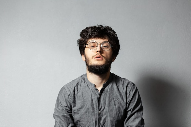 Portrait of self-confident bearded guy with disheveled hair and glasses