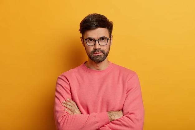 Portrait of self confident serious male entrepreneur keeps hands crossed