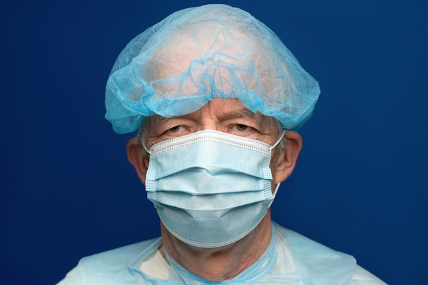 Portrait of senior adult dressed in surgical face mask with ear straps, covering nose and mouth from sars, virulently infectious disease corona virus. man in medical clothes on classic blue background