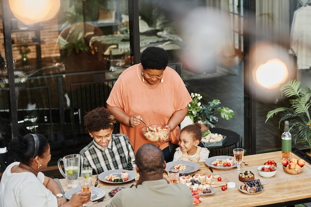 Portrait of senior africanamerican grandma serving food at family dinner outdoors copy space