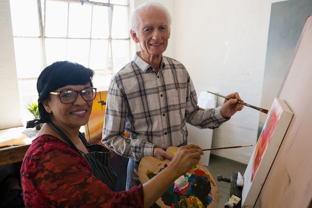 Portrait of senior artists painting on canvas