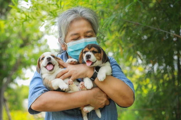 Portrait of senior asia woman with protective mask and with her puppy dog playing at the park.