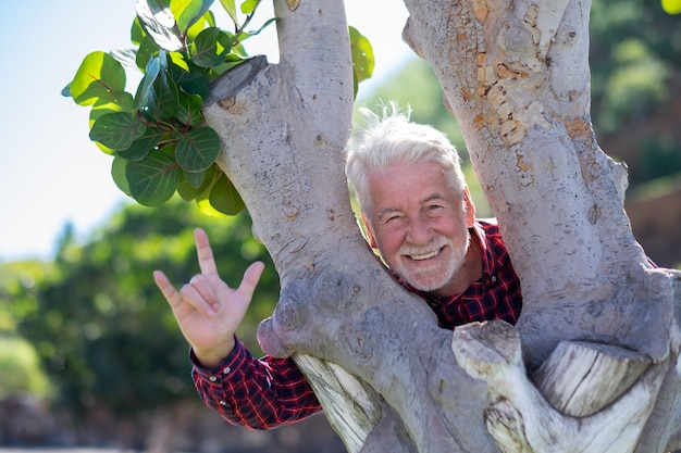 Portrait of a senior bearded man enjoying outdoors in a public park standing between two tree trunks. joyful elderly with white hair and checkered shirt
