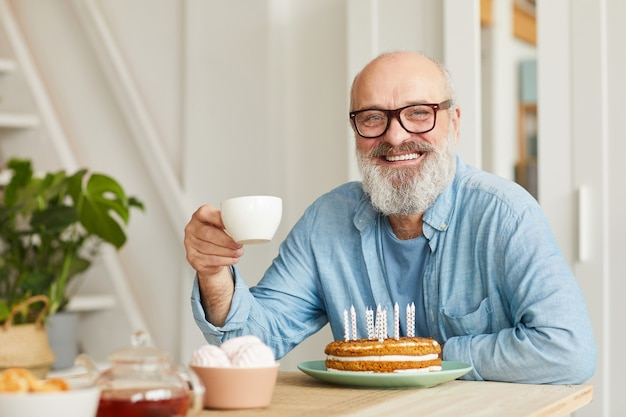 Portrait of senior bearded man in eyeglasses sitting at the table with birthday cake drinking tea and smiling at camera