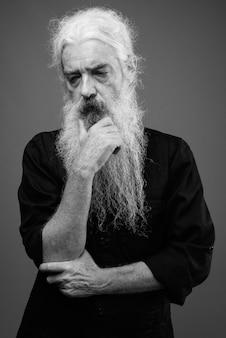 Portrait of senior bearded man wearing black shirt on gray in black and white