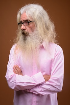 Portrait of senior bearded man wearing pink shirt and thinking