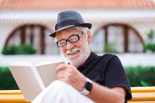 Portrait of a senior bearded man with hat sitting on a bench in the park relaxing and reading a book