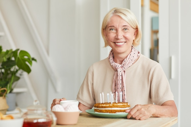 Portrait of senior blonde hair smiling at camera while sitting at the table with tea and cake