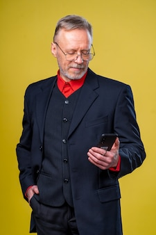 Portrait of senior businessman holding in hands phone while standing at studio
