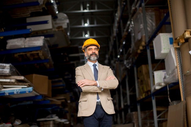 Portrait of senior businessman in suit with helmet in a warehouse