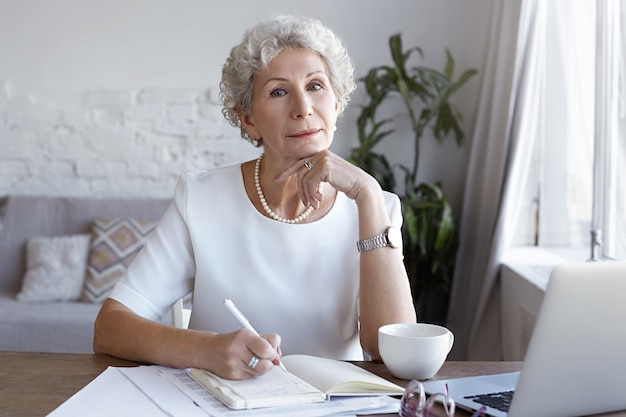 A portrait of senior businesswoman working indoor