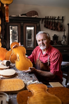 Portrait of senior carpenter in his old-fashion workshop making violins music instrument for academy of arts