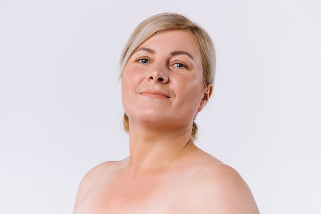 Portrait of a senior contented woman with clean and fair skin on a white background. a natural