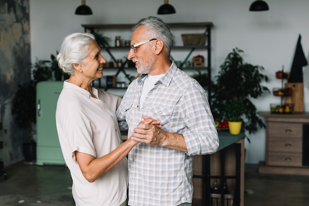 Portrait of senior couple dancing together in kitchen