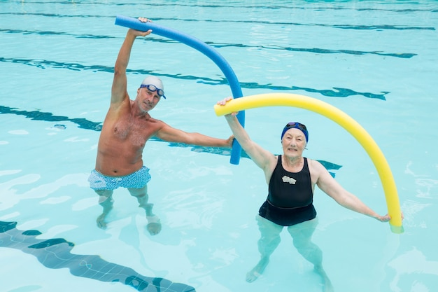 Portrait of senior couple exercising with pool noodle in swimming pool