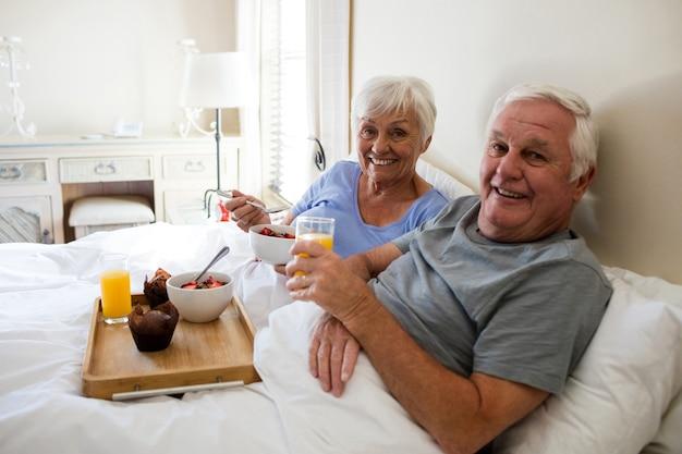Portrait of senior couple having breakfast in the bedroom at home