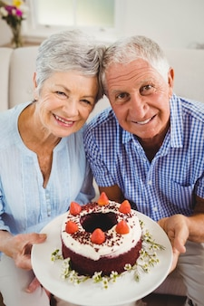 Portrait of senior couple holding a cake and smiling in living room