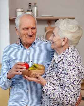 Portrait of senior couple holding fruits