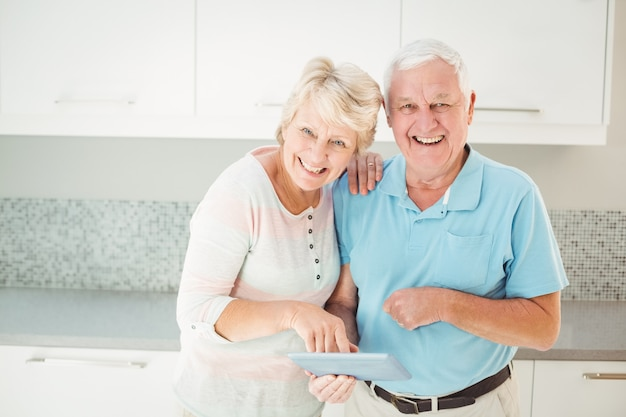 Portrait of senior couple laughing with tablet in kitchen