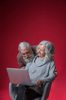 Portrait of senior couple looking at laptop against red background