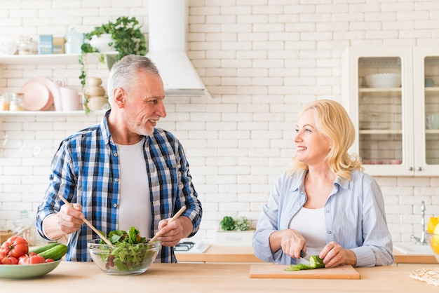 Portrait of a senior couple preparing the salad in the kitchen
