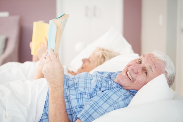 Portrait of senior couple reading on bed
