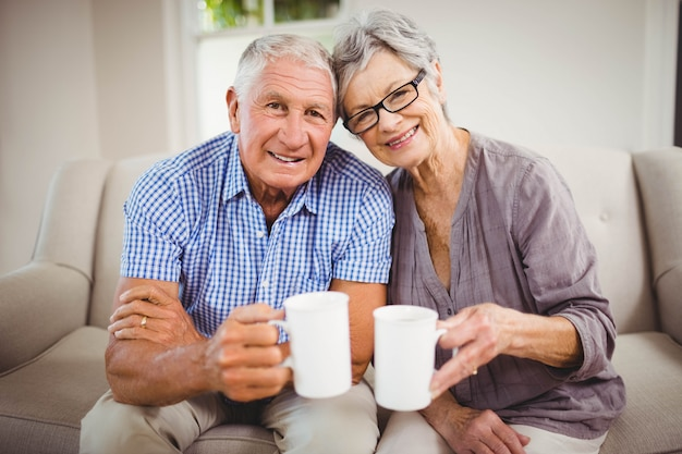 Portrait of senior couple sitting on sofa and having coffee in living room
