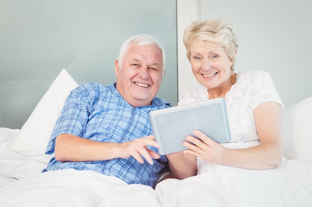 Portrait of senior couple using tablet on bed