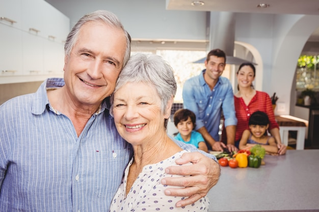 Portrait of senior couple with family preparing food in background