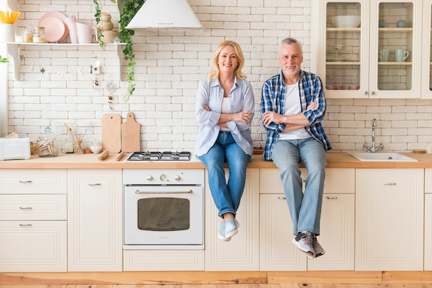Portrait of a senior couple with their arms crossed sitting on kitchen counter