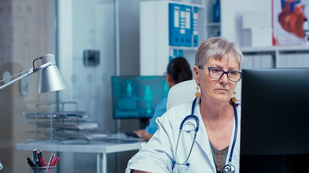 Portrait of senior doctor woman working on pc in modern private cabinet while the nurse is checking x rays in the back and other medical stuff walks in hallway. consulting in healthcare system