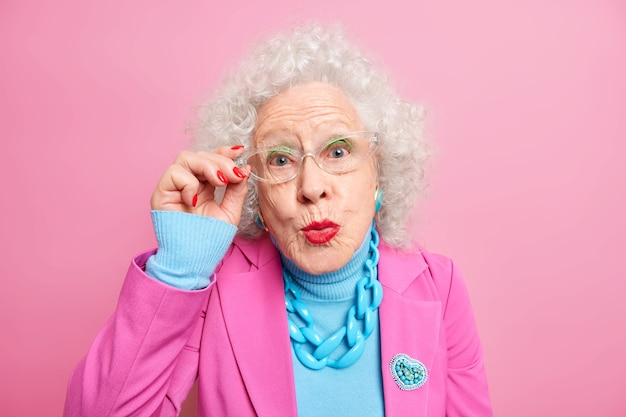 Portrait of senior european woman with curly grey hair keeps hand on rim of spectacles keeps lips rounded dressed in fashionable clothes
