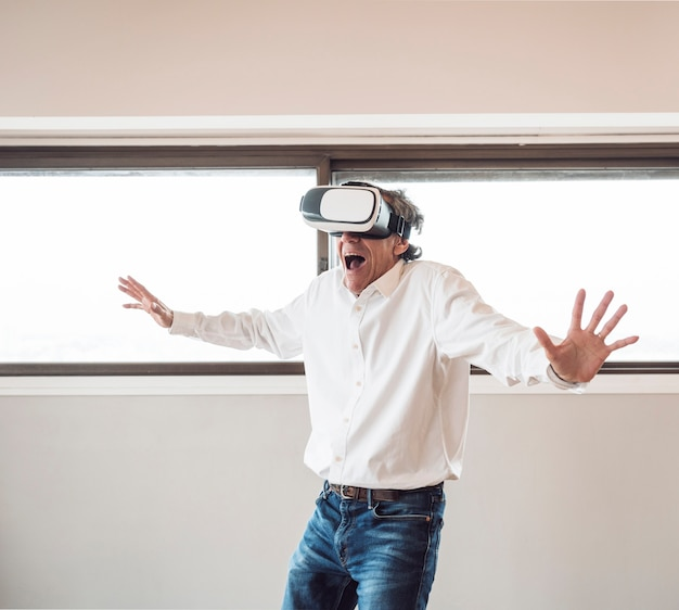 Portrait of senior excited man experiencing virtual reality