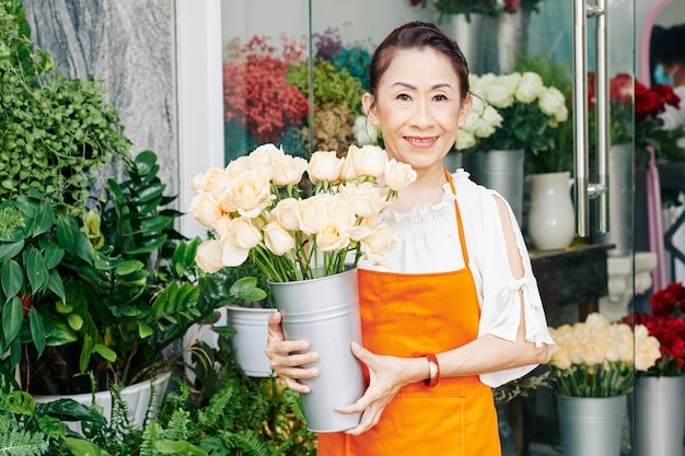 Portrait of senior florist standing at entrance of her flower shop with bucket of fresh white roses