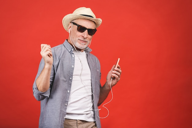 Portrait of senior happy cheerful elderly man dancing and listening music witn phone and headphones  isolated.