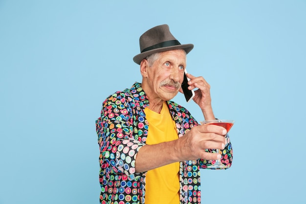 Portrait of senior hipster man using devices, gadgets isolated on bright studio background. tech and joyful elderly lifestyle concept.