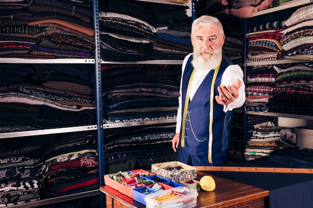 Portrait of a senior male fashion designer inviting someone in his shop