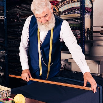 Portrait of a senior male fashion designer measuring fabric with wooden ruler