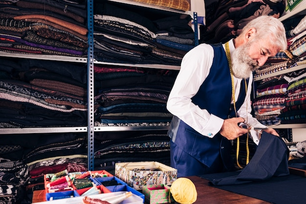 Portrait of a senior male tailor cutting a piece of fabric with scissors