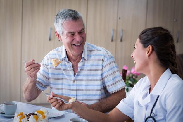 Portrait of senior man and female doctor having cake in living room