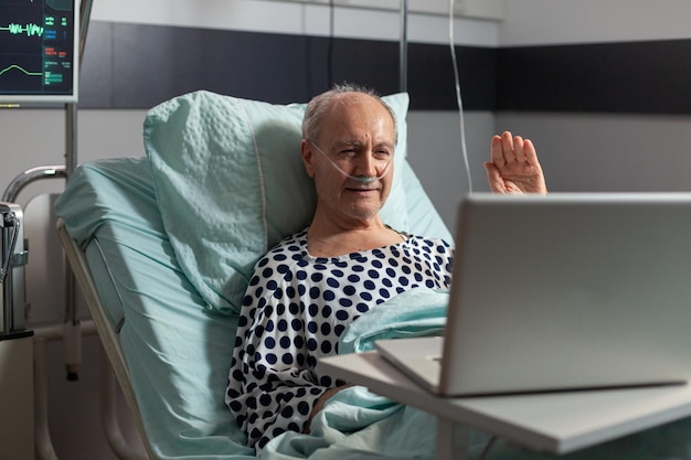 Portrait of senior man greeting family waving at laptop camera laying in hospital bed, after illness diagnosis, breathing with oxygen tube. modern eqipment monitoring pacient heart rate during recover