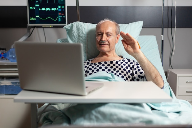 Portrait of senior man greeting family waving at laptop camera laying in hospital bed after illness ...